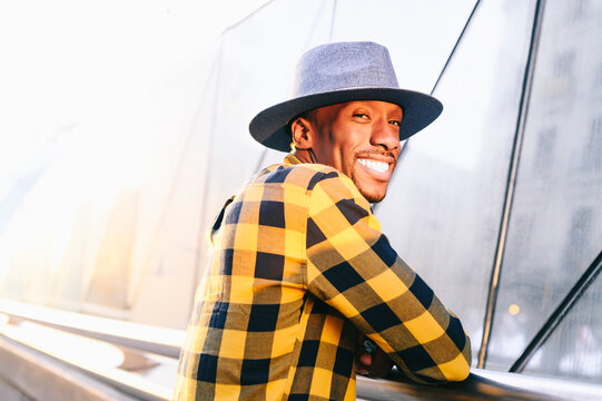 Happy african man in yellow plaid shirt standing in city during sunset