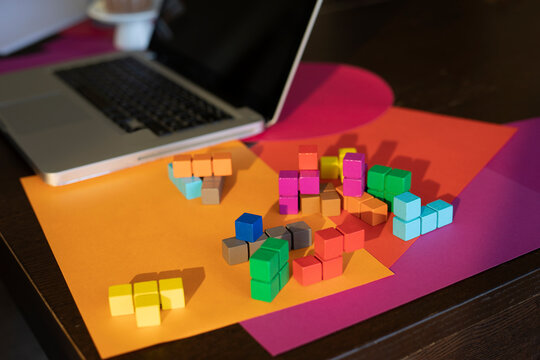 High angle view of multi colored paper, laptop and colorful blocks on table