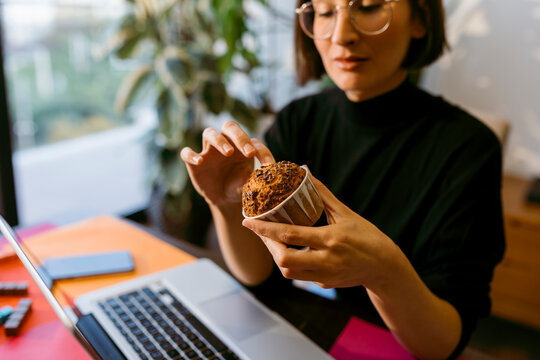 Businesswoman holding cake while sitting by laptop at home