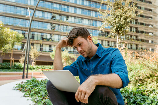 Confused young businessman using laptop while sitting against office buildings