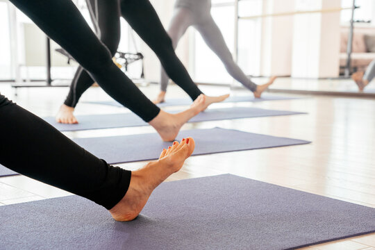 Cropped view of girls exercising yoga doing feet and legs stretching standing in a row