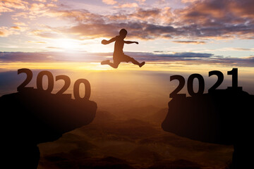 Success 2021 new year concept..Silhouette man jump between 2020 with hills and sky sunset background Wall mural
