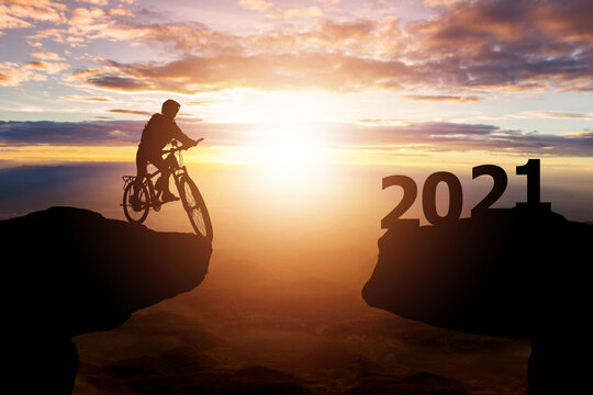 Success 2021 new year concept. Silhouette of cyclist riding between 2020 years with sunset background