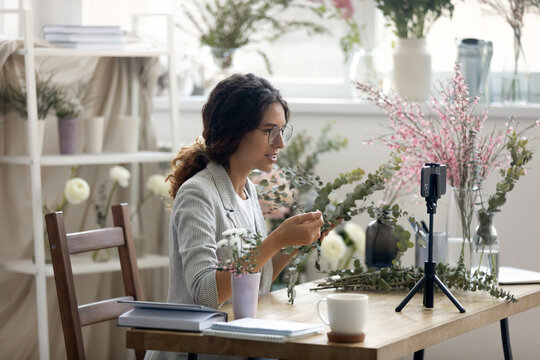 Do it yourself. Enthusiastic young woman giving professional course webinar by flower arranging. Florist recording video lesson on smartphone webcam at creative studio. Promoting hobby business online