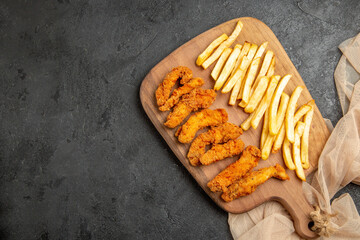 Fried chicken meal cooked along with potatoes on wooden cutting board on dark background Fotobehang
