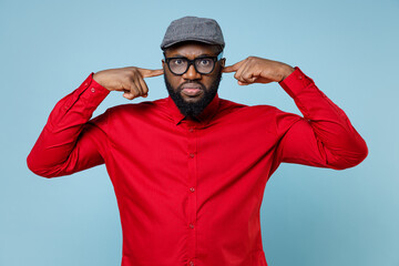 Concerned young bearded african american man 20s wearing casual red shirt eyeglasses cap standing covering ears with fingers looking camera isolated on pastel blue color background studio portrait.