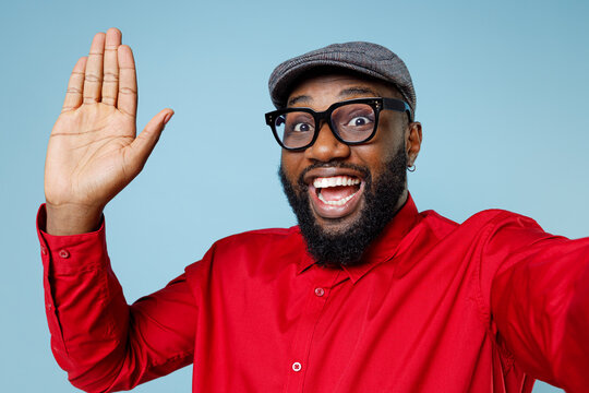 Close up of excited young bearded african american man in red shirt eyeglasses cap doing selfie shot on mobile phone waving greeting with hand isolated on pastel blue color background studio portrait.