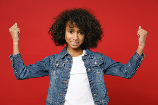 Smiling strong little african american kid girl 12-13 years old in casual denim jacket showing biceps muscles isolated on red color background children studio portrait. Childhood lifestyle concept.