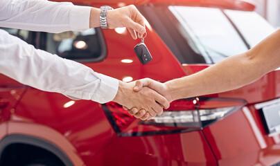 Fototapeta Crop dealer with car keys shaking hand of client obraz