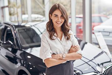 Obraz Confident female dealer standing near car - fototapety do salonu