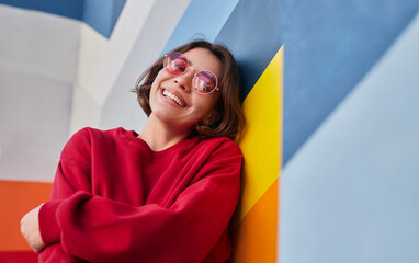 Happy female hipster leaning on colorful wall