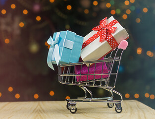Grocery shopping cart with  wrapped holiday gift boxes inside on defocus lights and cgristmas tree background