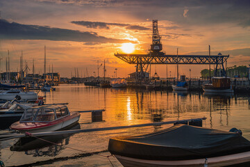 Colorful sunset above the sea with sail boats in Germany, Rostock. Reflected sun on a water surface. Seascape, Summer and travel vacation concept
