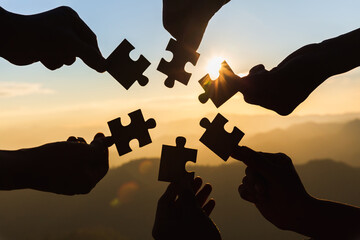 Silhouette of hand holding Jigsaw with Sunrise background. . symbol of association and connection. business strategy. Wall mural