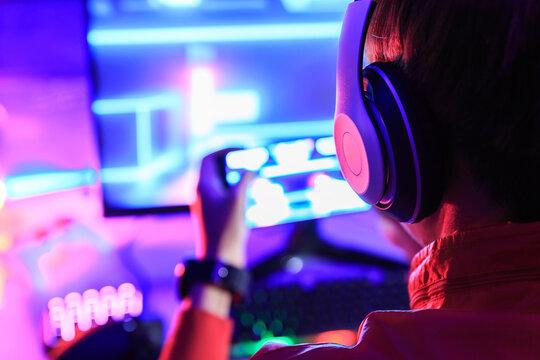 Gamer playing online game via smart phone in dark room