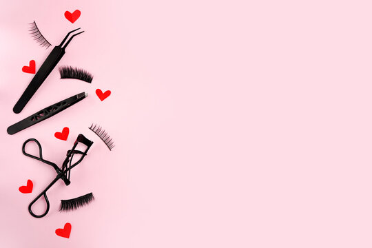 Lash curler, false lashes and tweezers for eye make-up on pink background with red hearts , copy space