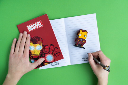 Minsk, Belarus. December, 2020. Popular Super Heroes Marvel. Iron Man. Notebooks, copybook, pen, Lego constructor. Education and school background.