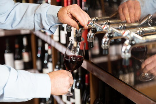 Bartender hand pouring draught red wine to glass. High quality photo