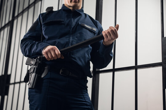 A strict prison guard in uniform guards cells with prisoners in a maximum security prison