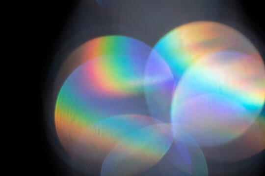 Lens flare, abstract bokeh lights. Reflection from glass or jewelry. Defocused shining colorful spots. Optical iridescent lens effect.
