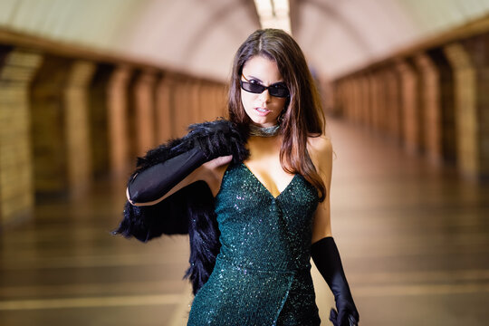 seductive woman in black lurex dress and sunglasses holding faux fur jacket while posing at metro station