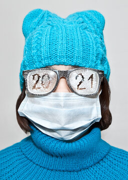 A girl in a medical mask and glasses with the date 2021 scrawled on it. Happy new year.