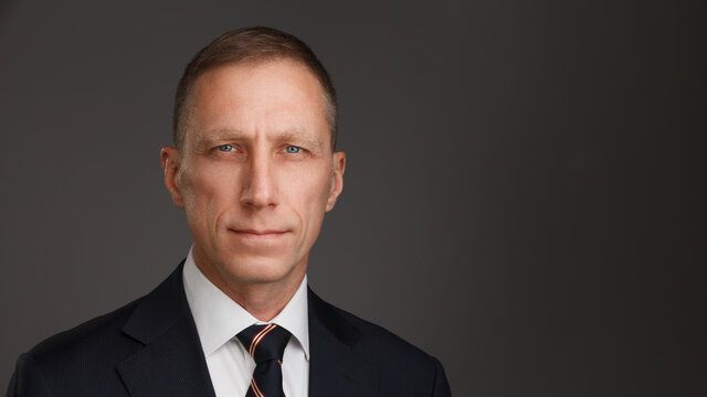 Portrait of a serious man in suit and tie looks at the camera. Male headshot