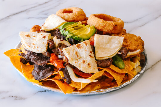 Stacked nachos with beef onion rings and tortillas