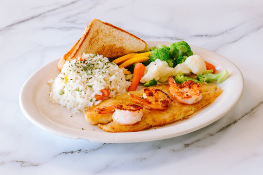 Mexican food grilled fish with shrimp steamed vegetables rice and toast