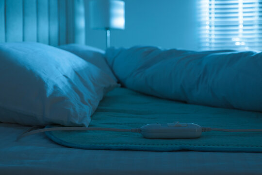 Bed with electric heating pad indoors at night