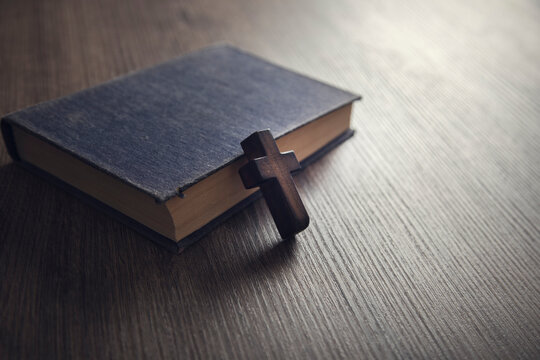 cross on the Bible on a wooden background