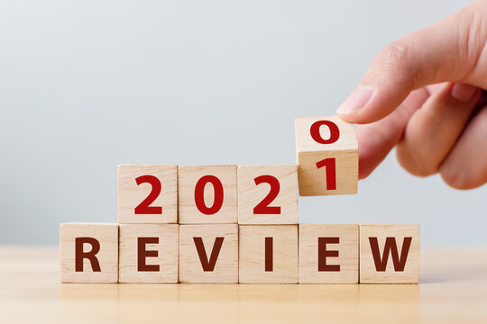 2021 review concept. Hand flip wood cube change year 2020 to 2021 and the word REVIEW on wooden block on wood table