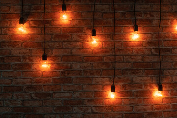 Some lightbulbs are hanging over a brick wall