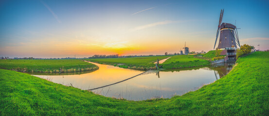 Traditional dutch scenery with windmills at sunset. Netherlands countryside