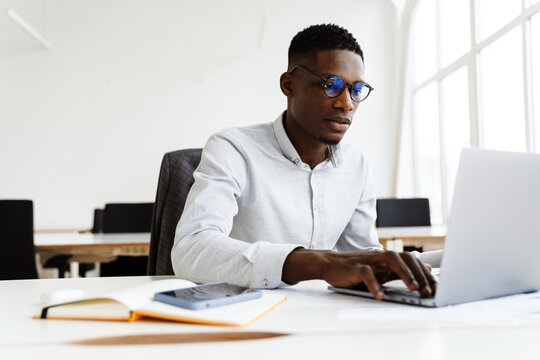 Afro american focused man in eyeglasses working with laptop