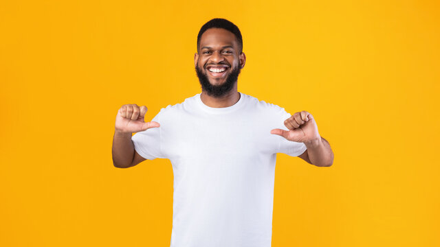 Happy African Man Pointing Thumbs At Himself Over Yellow Background
