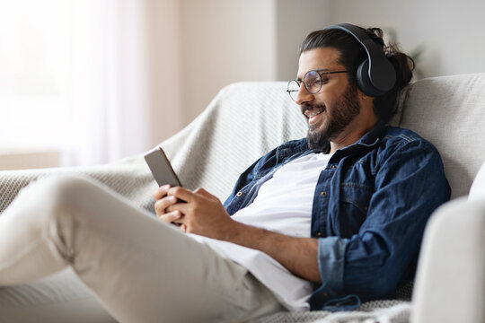 Home Leisure. Young Eastern Guy In Headphones Relaxing With Smartphone On Couch