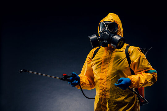 Portrait of a man in a yellow chemical protection suit holding a sprayed disinfectant