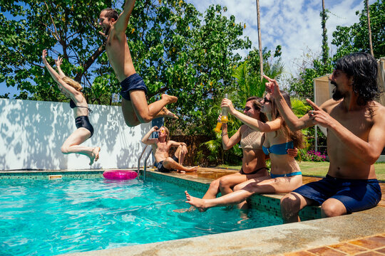 young multiethnic group of friends having fun on swimming pool party when outbreak covid spreading is in the air