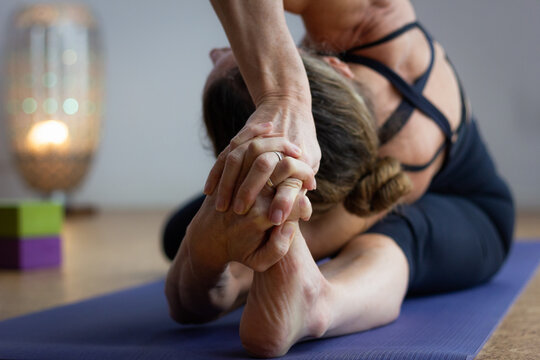 Flexible yogi leaning head towards left leg and hands holding foot in studio. Woman in black outfit practices ashtanga yoga parighasana pose of intermediate series. Advanced practitioner concept