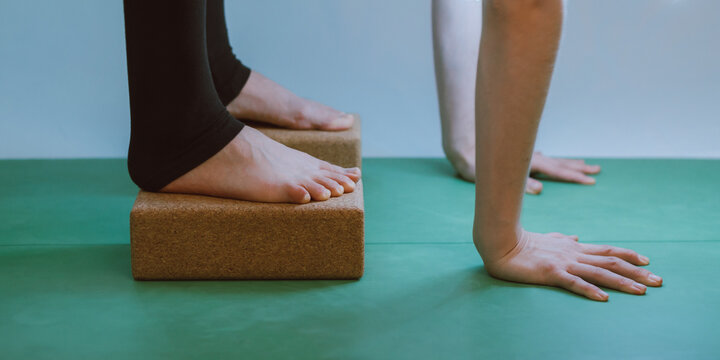Hands and feet on cork blocks of a woman doing a yoga forward fold, green yoga mat, white background