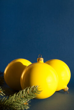 Yellow Christmas decorative balls on blue background with long shadows. Christmas composition. Winter holiday theme