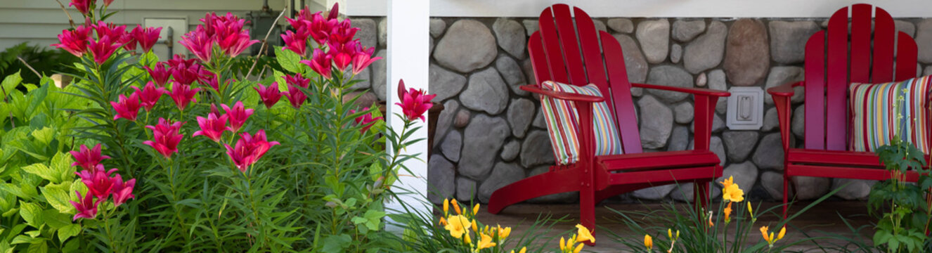 Vivid red stargazer lily coordinates perfectly with the red adirondack chairs on the front porch of this Michigan home.