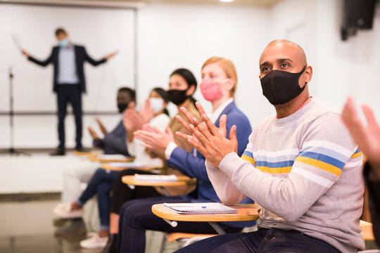 Hispanic man in protective face mask sitting in conference room during business seminar, applauding speaker. New normal during coronavirus pandemic..
