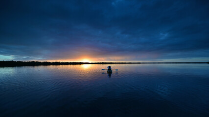 Distant kayaker at sunset on Coot Bay in Everglades National Park, Florida under winter cloudscape reflected in tranquil water.