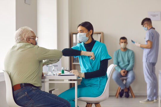 Young nurse in face mask bumping elbows with senior man before giving him vaccine