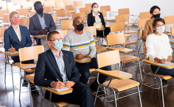 Multiethnic group of people wearing protective masks sitting in conference room keeping distance during business training. Precautions during mass events in coronavirus pandemic