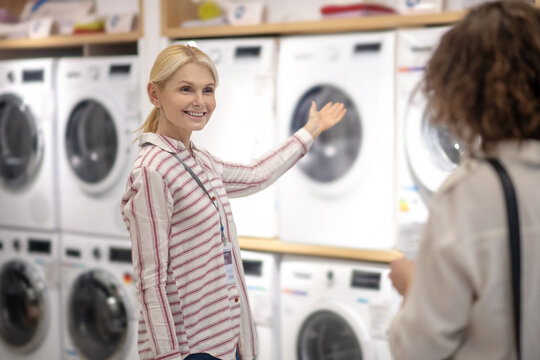 Sales assistant in striped shirt showing new washing machines to the customer