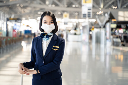 Portrait of air hostess wearing face mask, stand and looking at camera