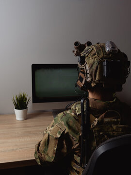 US Army special forces operator looking at the computer screen in the office. Seal team operator in full gear.